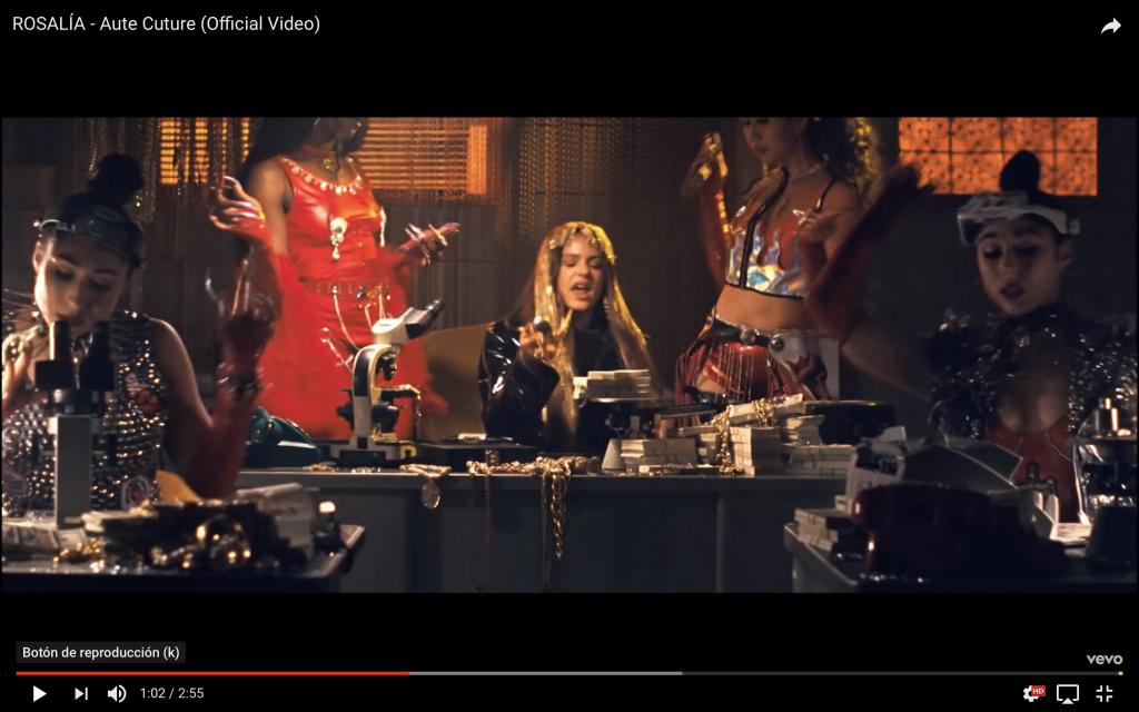 Captura de vídeo de Rosalía en la que aparece como jefa de un compro oro, con una peluca de cadenas emulando a Cleopatra.