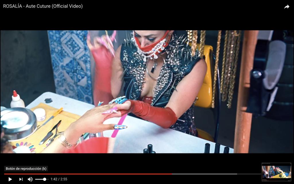 Captura del vídeo de Rosalía en el que aparece una mujer con un chaleco de piel lleno de tachuelas haciendo la manicura a otra mujer.